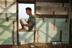 Asri rests In the window of his partly built home.  Many Lampuuk families who refused to leave have started to rebuild their lives beginning with simple homes of wood rescued from the drifts left by the tsunami.