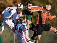 SOUTHBURY, CT - 19 OCTOBER 2009 -101909JT12-.New Milford's goalie Jack Holub punches the ball away from the goal as his teammate Zane Swanson jumps for the ball along with Pomperaug's #14 Connor Kennedy, #12 Matt Ruston and #19 Kyle Molnar during Monday's game at Pomperaug. New Milford won, 2-0..Josalee Thrift Republican-American