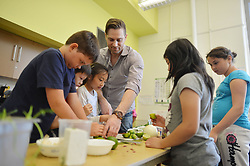 June 3, 2013 - Toronto, ON, Canada - TORONTO, ON - JUNE 3  -  Chef Cory Vitiello from the Harbord Room Restaurant helps kids from Dovercourt Public School prepare the ingredients for what will become braised chicken tacos with tomatillo sauce on June 3, 2013. As part of Luminato chefs will be teaching locals kids a bit about cooking. Carlos Osorio/Toronto Star (Credit Image: © The Toronto Star/ZUMAPRESS.com)