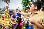 12 APRIL 2013 - BANGKOK, THAILAND:   <br />  Thais sprinkle scented oils on the Phra Buddha Sihing while it is paraded through the streets of Bangkok on the first day of Songrkran. The Phra Buddha Sihing, a revered statue of the Buddha, is carried by truck through the streets of Bangkok so people can make offerings and bathe it in scented oils. Songkran is celebrated in Thailand as the traditional New Year's Day from 13 to 16 April. The date of the festival was originally set by astrological calculation, but it is now fixed. If the days fall on a weekend, the missed days are taken on the weekdays immediately following. Songkran is in the hottest time of the year in Thailand, at the end of the dry season and provides an excuse for people to cool off in friendly water fights that take place throughout the country. The traditional Thai New Year has been a national holiday since 1940, when Thailand moved the first day of the year to January 1. The first day of the holiday period is generally the most devout and many people go to temples to make merit and offer prayers for the new year. PHOTO BY JACK KURTZ