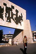 A street photographer pauses in Baghdad beside a Modernist sculpture