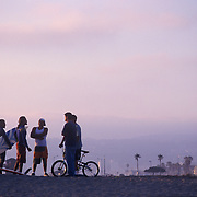 Group of five young men on the beach at sunset, small in composition, two surfboards, one bike. Ocean Beach, CA.