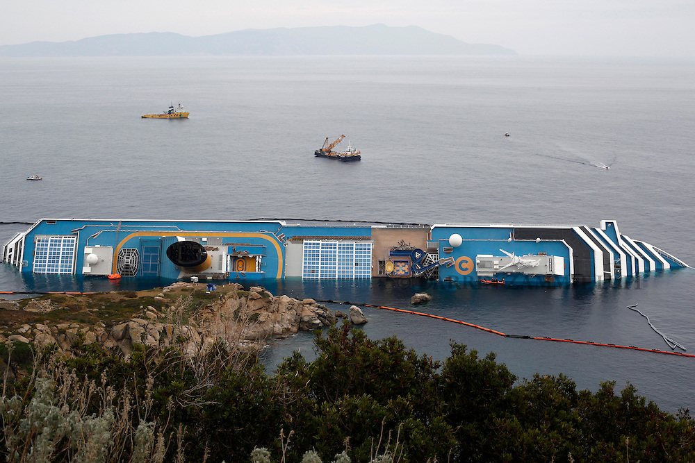 The cruise liner Costa Concordia lies on its side off the west coast of Italy at Giglio island January 31, 2012. Italian authorities have ended the search for bodies on the submerged sections of the capsized Costa Concordia, more than two weeks after the giant cruise liner capsized off the Tuscan coast, officials said on Tuesday....REUTERS/Darrin Zammit Lupi (ITALY)