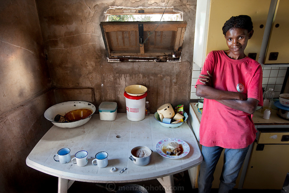 Marble Moahi, a mother living with HIV/AIDS, in the family kitchen in Kabakae Village, Ghanzi, Botswana with her typical day's worth of food and antiretroviral medications.  (From the book What I Eat: Around the World in 80 Diets.) The caloric value of her day's worth of food on a typical day in March was 900 kcals. She is 32 years of age; 5 feet, 5 inches tall; and 92 pounds.  Despite a decline in new HIV infections in sub-Saharan Africa, this region of the world remains the most heavily impacted by HIV/AIDS. . MODEL RELEASED.