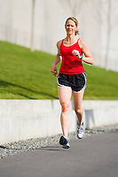 Caucasian woman (Angel) running in urban settings for the DrTri workout video cover art.