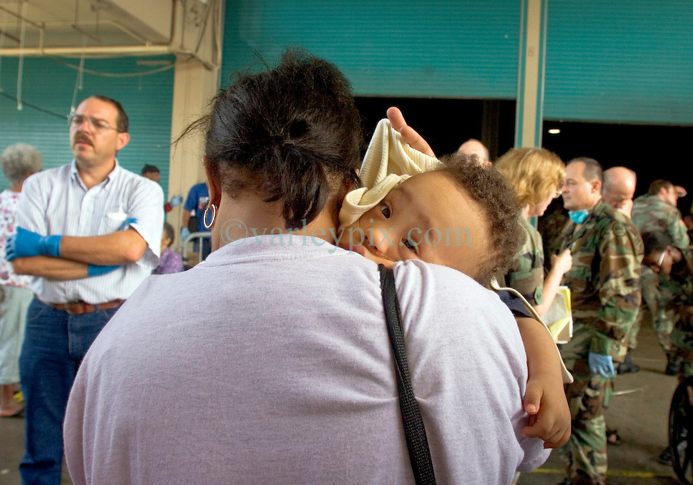 30 August, 2005. New Orleans Louisiana. Hurricane Katrina aftermath. <br /> Rescued from the flooded lower 9th ward by the Louisiana National Guard, a young mother carries her very sick baby to safety at the makeshift hospital triage unit set up at the Superdome in New Orleans.<br /> Photo Credit: Charlie Varley/varleypix.com