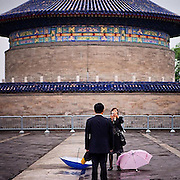 """Woman taking a photograph of her husband at """"The Temple of Heaven"""" which is a complex of Taoist buildings situated in the southeastern part of central Beijing, China. #latergram #china #beijing #photography #couple #temple #umbrella #colors #past #camera"""