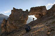 """Two photographers at a rock arch called """"Sonnentor"""", Julier, Parc Ela, Grisons, Switzerland"""