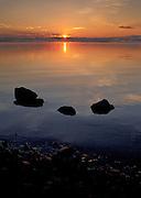 The sun sets casts warm orange light on Yellowstone Lake, Yellowstone National Park, Wyoming