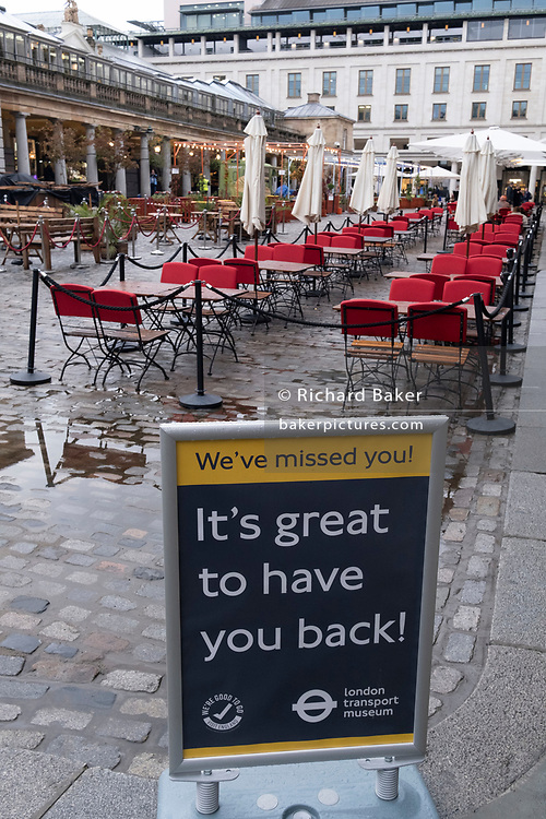 A transport Museum sign welcomes visitors back and empty seating awaits bar and restaurant customers on a wet and rainy day in Covent Garden during the second wave of the Coronavirus pandemic and when the capital is designated by the government as a Tier 2 restriction, on 21st October 2020, in London, England.