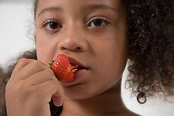 Portrait of young girl eating a strawberry,
