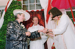 Mature Lesbian wedding ceremony with partners exchanging rings before priest,