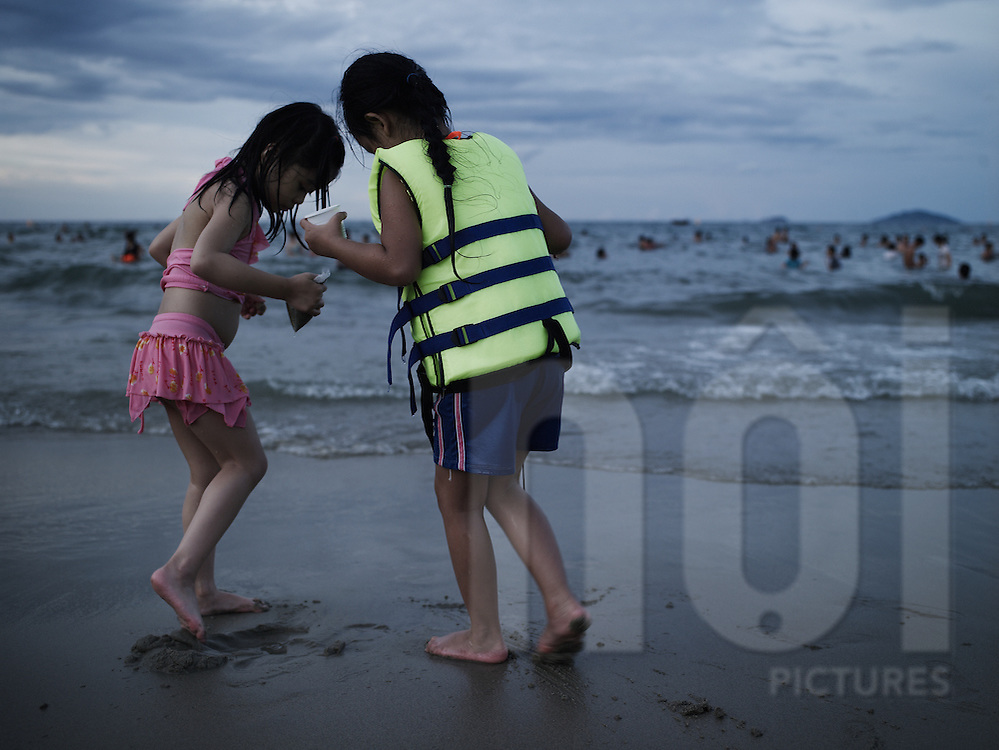Two little vietnamese girls play in the sand of a beach along the shore of Hoi An, Vietnam, Asia