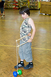 Young boy practising tricks with diablo in school sports hall,