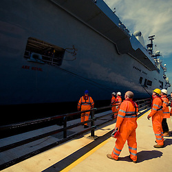 As HMS Ark Royal docks the workmen on the cruise terminal perpare to tie up the ropes and set to work on the gangways.