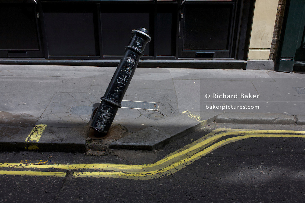 Leaning traffic post and twisting double-yellow lines in Soho, central London.