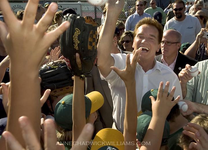 "Gov. Arnold Schwarzenegger hands out baseballs to Auburn little leaguers at Beggs Field in Auburn as he kicks off his ""Protecting the California Dream Tour"" on June 7, 2006."