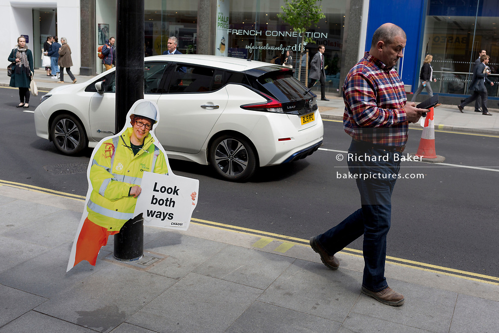 A broken warning construction work figure - one of many up and down both sides of the Tottenham Court Road, warns pedestrians of a change of road layout, from one-way to two-way traffic, on 7th May 2019, in London, England.