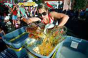 SHOT 9/22/2007 - Joanna Swartz, 29, of Denver pours beer from 12 steins into a bucket during a stein carrying contest at the 38th Annual Oktoberfest in Denver, Co. Swartz came in second place in the contest. Modeled after Oktoberfest in Munich Germany, Oktoberfest on Larimer Street commemorates this world-famous and time-honored tradition of German heritage. The festival has truly become a Denver mainstay offering German attractions, music from national touring groups, performances by international dancers, children?s activities, heritage booths selling German good, splendid décor, and accordion concert, and authentic cuisine. Oktoberfest Denver will move from its previous home on Larimer Square to Denver?s Ballpark Neighborhood. The new site, on Larimer Street between 20th and 22nd..(Photo by Marc Piscotty © 2007)