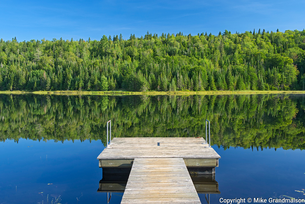 Tree reflection and dock in Lac Modène<br />La Mauricie National Park<br />Quebec<br />Canada