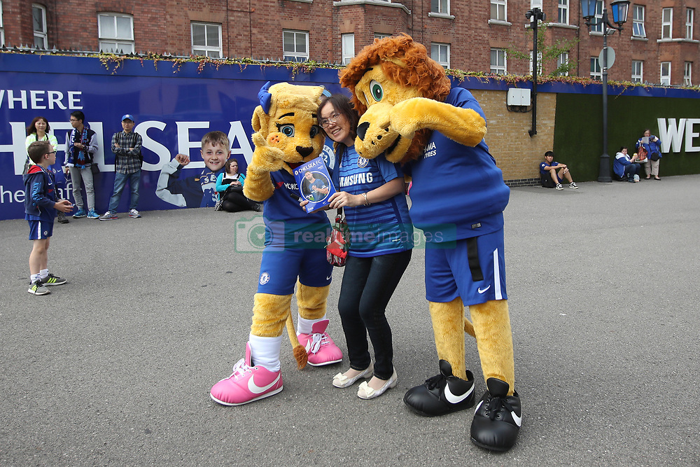 A Chelsea supporter poses with Chelsea mascots Stamford the Lion and Bridget the Lioness signs an autograph for a Chelsea supporter before the Premier League match at Stamford Bridge, London.