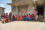 Members of the Shree Khanideri Sanokishan Krishi Sanakari Women's Co-operative hold a meeting outside a store in the centre of their village, Kakani, Nuwakot District, Nepal