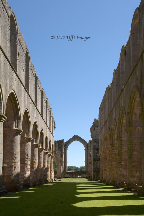 Yorkshire, Fountains Abbey ruins; looking west down the empty nave, with shadow pattern from the columns.