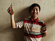 Portrait of Vietnamese boy wearing a silver necklace and happily showing off a handmade artisan shuttlecock, Nghe An, Vietnam, Southeast Asia