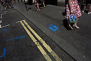 "Blue stencilled painted words saying ""trial Hole"" seen on London street pavement."