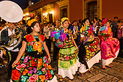Young women dressed in traditional costumes process in a comparsas past the Santo Domingo de Guzmán Church during the Day of the Dead Festival known in Spanish as Día de Muertos on November 2, 2013 in Oaxaca, Mexico.