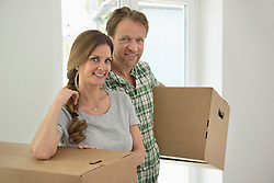 Couple working carrying boxes new home