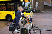 In Utrecht fietst een vrouw al bellend op de fiets door de binnenstad.<br /> <br /> In Utrecht a woman is cycling atthe city center while phoning.