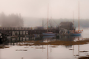 SUBJECT: a wharf in Boothbay, Maine. IMAGE: still tidewater quietly reflects boats, masts and dock while the mist adds mystery and atmosphere to the sepia tones