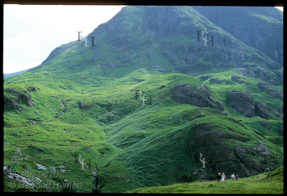 People hike along trail through lush mountain pastures in upper Glen Coe on a July afternoon; Glencoe, Scotland.