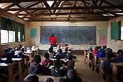 A teacher stands at the front of the class teaching English to a year 3 class. The school consists of 6 teachers with approximately 60 children in each class.  Undugu Society of Kenya (USK) are an NGO who run various programmes to help the school and pupils including a lunchtime feeding program.