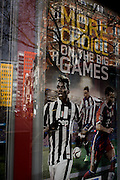 Football theme window showing team players in betting business window, central London.