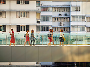 "27 MARCH 2015 - BANGKOK, THAILAND: Shoppers walk on a skywalk the connects two wings of ""EmQuartier,"" a new mall in Bangkok. ""EmQuartier"" is across Sukhumvit Rd from Emporium. Both malls have the same corporate owner, The Mall Group, which reportedly spent 20Billion Thai Baht  (about $600 million US) on the new mall and renovating the existing Emporium. EmQuartier and Emporium have about 450,000 square meters of retail, several hotels, numerous restaurants, movie theaters and the largest man made waterfall in Southeast Asia. EmQuartier celebrated its grand opening Friday, March 27.    PHOTO BY JACK KURTZ"