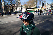 Toursist uses a London branded bag as an improvised sun shield to protect her head form the sunshine. London, England, United Kingdom.
