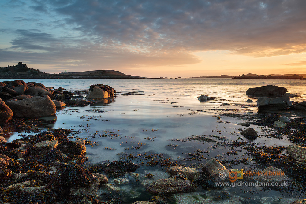 First light illuminates foreground rocks at Old Grimsby Harbour on Tresco, Isles Of Scilly, Cornwall, UK.