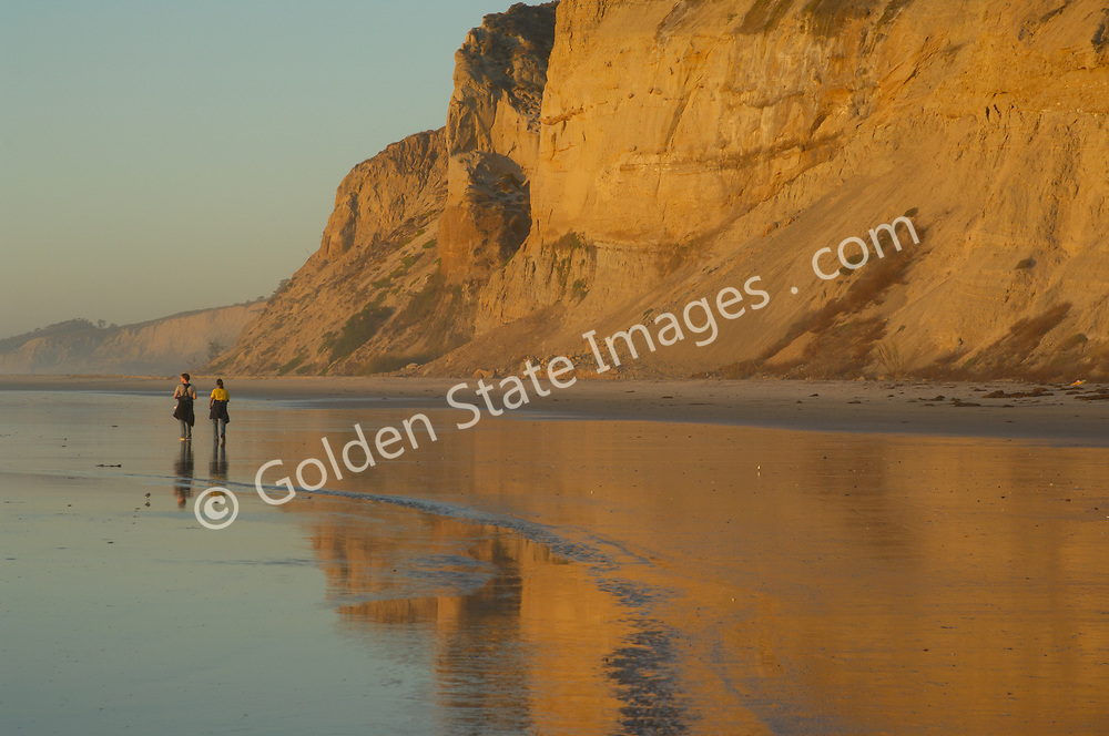 Couple walking along the beach just at sunset.