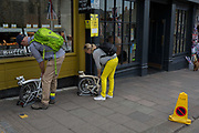 Two cyclists fold-up their Brompton bikes in Windsor High Street, on 14th May 2018, in London, England.