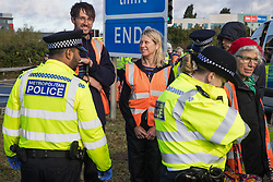 Colnbrook, UK. 27th September, 2021. Metropolitan Police officers arrest Insulate Britain climate activists who had previously blocked a M25 slip road at Junction 14 close to Heathrow airport as part of a campaign intended to push the UK government to make significant legislative change to start lowering emissions. The activists are demanding that the government immediately promises both to fully fund and ensure the insulation of all social housing in Britain by 2025 and to produce within four months a legally binding national plan to fully fund and ensure the full low-energy and low-carbon whole-house retrofit, with no externalised costs, of all homes in Britain by 2030.