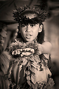 A picture from Waikiki showing a young girl dancing the hula with outstretched arms.