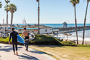 Surfers with Longboards Walking to the San Clemente Pier