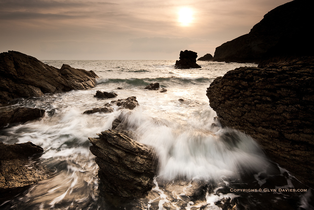 Waves at sunset, crashing into the small rocky cove at south of South Stack on Holy Island, Anglesey, Wales,