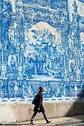Young woman passing Azulejos Portuguese blue and white wall tiles of Capela das Almas de Santa Catarina  - St Catherine's Chapel in Porto, Portugal