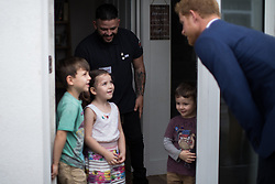© Licensed to London News Pictures . 04/09/2017 . Manchester , UK . Prince Harry meets father SIMON FLORES and his children KOBI FLORES (six) , LILLY-ANNE FLORES (five) and DAMASO FLORES (four) , during a visit to residents of the Walking With the Wounded ( WWTW) hub on Canada Street , Newton Health .  WWTW helps ex-service personnel with physical or mental health needs make the transition back to civilian life . The street was subject to an episode of DIY SOS when people gave their time and resource to help redevelop the houses . Photo credit : Joel Goodman/LNP