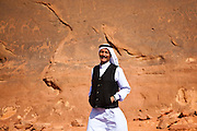 Zedane al-Zalabieh, owner and manager of the Bedouin Meditation Camp, with ancient petroglyph carvings of camels, in Wadi Rum, Jordan.