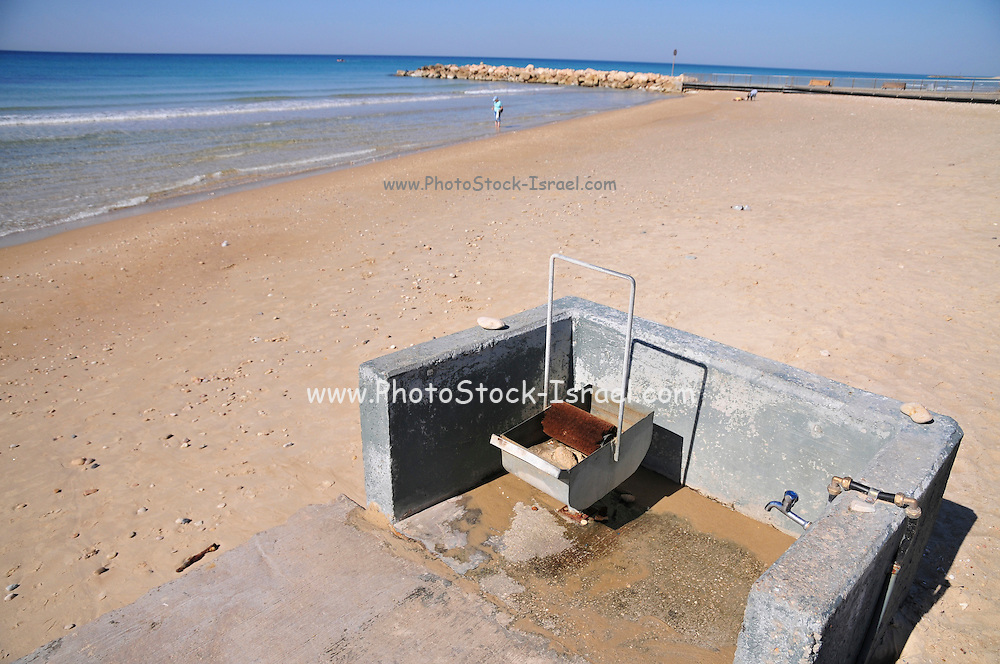 Israel. Haifa, Dado Beach, A device for cleaning tar of the feet of bathers. The device is a brush partially submerged in kerosene as a solvent