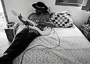 Blues guitarist Cool John Ferguson sits on his bed with his guitar.